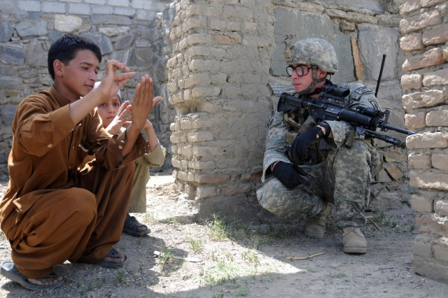 KUNAR PROVINCE, Afghanistan - U.S. Army Staff Sgt. Matthew R. Becker, of Sloatsburg, N.Y., the leader of 1st Squad, 1st Platoon, Company A, 2nd Battalion, 503rd Infantry Regiment, Task Force Rock, gives English counting lessons to young locals while receiving Pashtu lessons in return in the Noorgal District of eastern Afghanistan's Kunar province, April 17. His unit was in the village to take part in a female shura, which was attended by a female engagement team. (Photo by U.S. Army Spc. Albert L. Kelley, 300th Mobile Public Affairs Detachment)