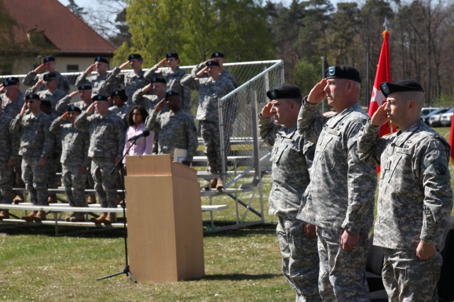 Command Sgt. Maj. David S. Stading, Brig. Gen. Jimmie Jaye Wells and Command Sgt. Maj. Michael E. Biere, left to right, salute the U.S. flag during a change of responsibility ceremony at Daenner Kaserne in Kaiserslautern, Germany, April 24. Wells presided over the ceremony to transfer authority from Stading to Biere.