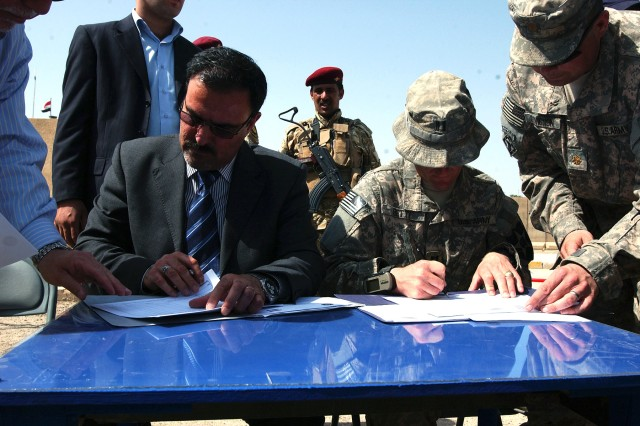 ABU GHRAIB, Iraq -, 1st Battalion 38th Infantry Regiment, 4th Stryker Brigade Combat Team, 2nd Infantry Division and Sameer Al-Haddad (left) from the Ministry of the Interior, sign documents transferring authority of Joint Coordination Center Abu Ghraib from U.S. forces to the Iraqi government April 20.(U.S. Army photo by Sgt. Bryce Dubee, 4th SBCT PAO, 2nd Inf. Div., USD-C)