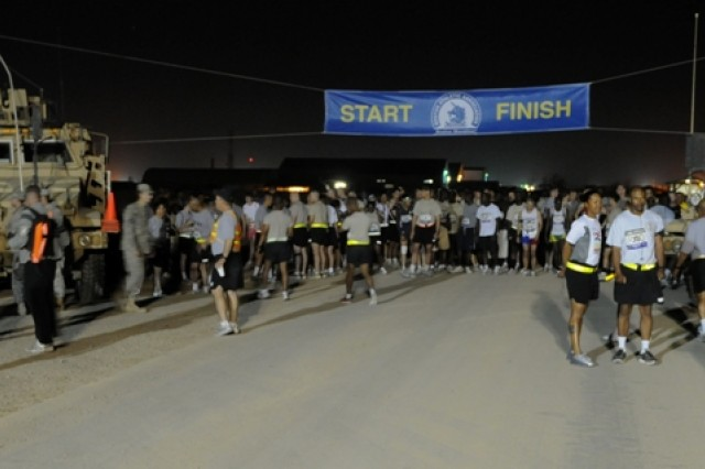 """Minutes before the """"oh-dark-hundred"""" start of the April 18, 2010, sixth-annual running of the Boston Marathon at Contingency Operating Base Adder, Iraq, 400 military and civilian runners from all over Iraq prep, posture and pose for photos. A fierce sandstorm postponed the previous day's running of the iconic contest."""