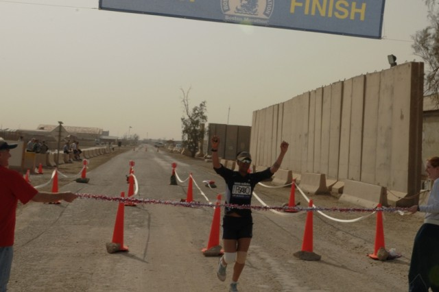 Battling sore knees, Denver, Col., native Spc. Janelle A. Drennan, 201st Battlefield Surveillance Brigade, breaks the tape April 18, 2010, with a time of 3:40:09, becoming the women's winner of the sixth-annual running of the Boston Marathon at Contingency Operating Base Adder, Iraq. Drennan said her first phone call would be to her father, who was her high school track coach.