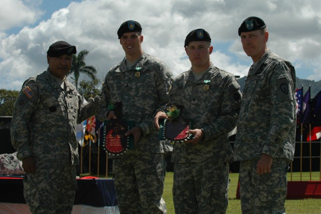 Sgt. Colin Whyte, a combat medic with Headquarters and Services Battery, 2nd Battalion, 11th Field Artillery Regiment, 2nd Brigade Combat Team (center left) and Spc. Andy James, a grenadier with Company B, 2nd Battalion, 27th Infantry Battalion, 3rd Brigade Combat Team (center right) receive shark-tooth warrior paddles and Army Commendation Medals from Maj. Gen. Bernard S. Champoux, commanding general, 25th Inf. Div. (far right) and Command Sgt. Maj. Frank M. Leota, command sgt. maj., 25th Infantry Division (far left) at the division's Best Warrior Competition awards ceremony April 26 at Sills Field, Schofield Barracks, Hawaii. Whyte and James won the division's Best Warrior Competition, in NCO and Soldier categories, respectively, and will represent the division at the USARPAC competition in June.