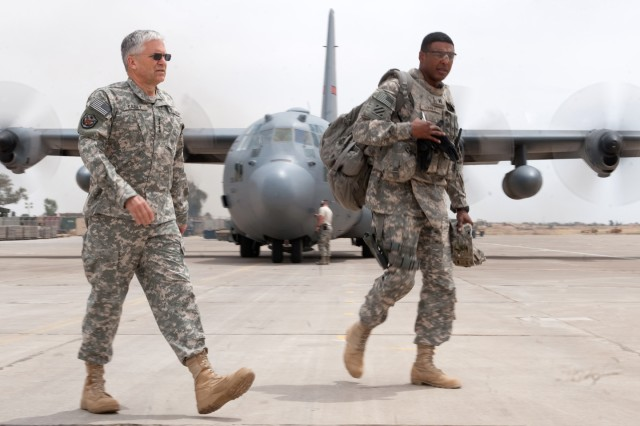 Chief of Staff of the Army Gen. George W. Casey Jr. passes a C-130 as he walks to a Black Hawk helicopter at Forward Operating Base Warrior, Kirkuk, Iraq, April 27, 2010. Casey is in Iraq to talk with Soldiers and meet with local military commanders.