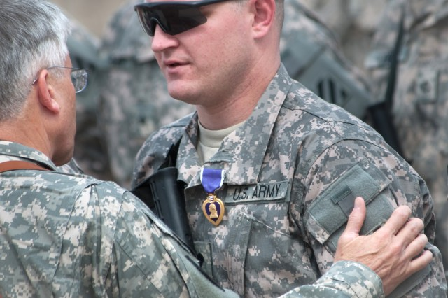 Gen. George W. Casey Jr., Chief of Staff of the Army, talks with a Soldier after presenting him with the Purple Heart medal at Forward Operating Base Marez in Mosul, Iraq, April 27, 2010.