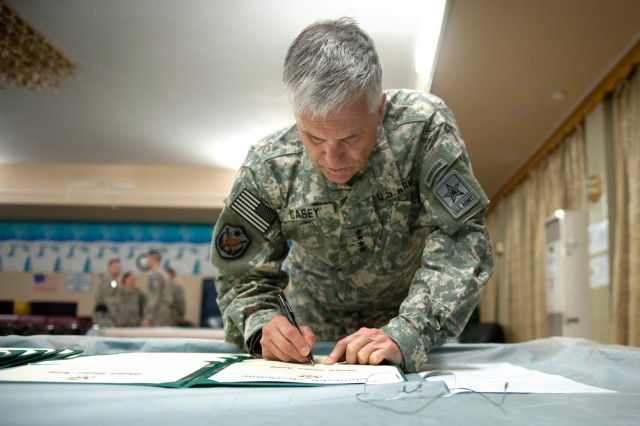 Chief of Staff of the Army Gen. George W. Casey Jr. signs awards and re-enlistment records at Forward Operating Base Marez in Mosul, Iraq, April 27, 2010. Casey visited Iraq to talk with Soldiers and meet with the local military leadership.