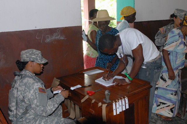 Sgt. Tammy Turner, a patient administrator with the 94th Combat Support Hospital, begins signing in patients following the opening ceremony of the Medical Readiness Training Exercise in Roche au Boteau, Haiti, April 26.