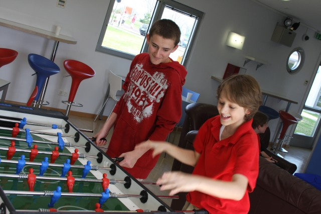 (From left) John Gray and Dustin Byrd, both of the Schweinfurt Middle School, know a thing or two about how to have fun. The new youth center, a million dollar project that took 13 months in the making, provides significant improvements like a technology lab, art and music room, kitchen, homework room and recreation area.