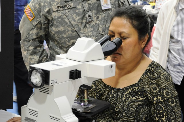 Siatu Peebles, whose husband is a military retiree, takes a close-up look at white blood cells through a microscope during the Retiree Expo and Health Fair Saturday at the Solomon Center. Staff Sgt. Marc Johnson, Moncrief Army Community Hospital, explains what she sees.