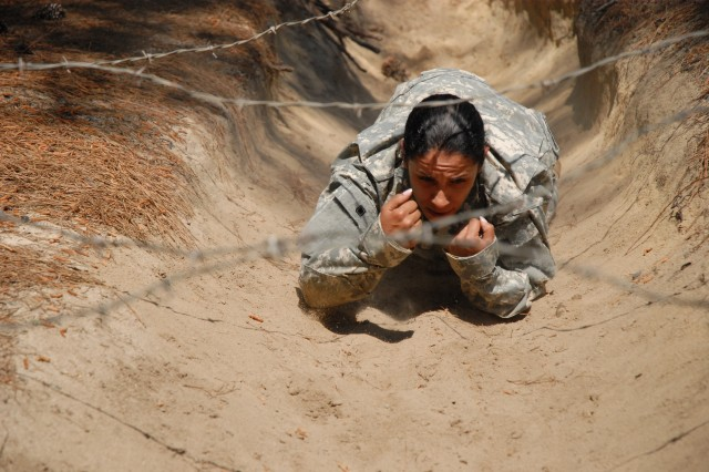 Staff Sgt. Daisy Martinez, Company C, 2nd Battalion, 60th Infantry Regiment, crawls under barbed wire as she negotiates the course.