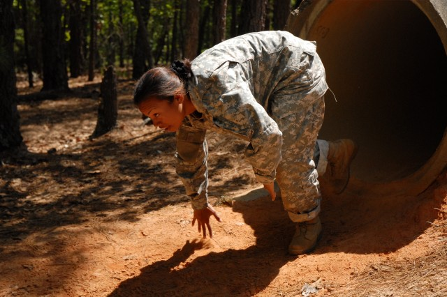 Staff Sgt. Kimberly Helgen, Company E, 3rd Battalion, 34th Infantry Regiment, runs through a cement culvert on the fourth day of the competition.