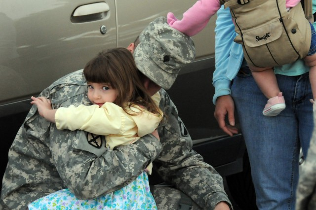 Spc. Kevin Delozier hugs his daughter, Katherine, 3, at the 164th TAOG deployment ceremony April 27 at Cairns Army Airfield.