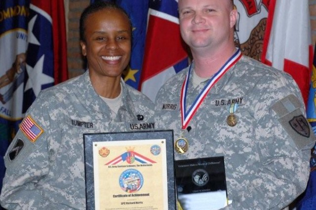 Spec. Richard Norris (R), assigned to the AFNORTH Battalion at JFC Brunssum, was named Military Volunteer of the Year for his work with the Boy Scouts, youth sports and his church. Lt. Col. Fern O. Sumpter, USAG Schinnen Commander, presented the award.
