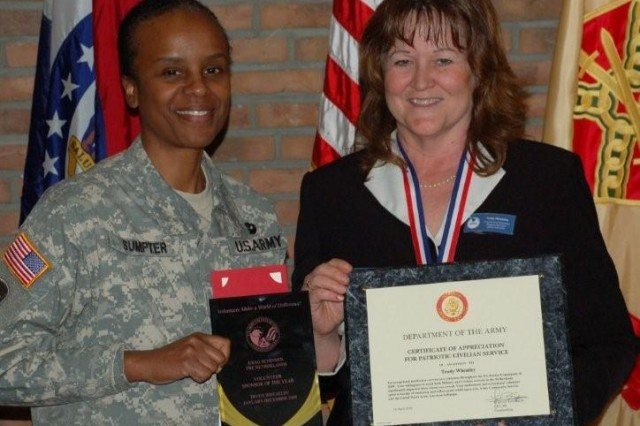 Trudy Wheatley received the Sponsor of the Year award from Lt. Col. Fern O. Sumpter, USAG Schinnen Commander, for her support to newcomers in the community. Wheatley's efforts resulted in faster in-processing and easier transitions so newcomers were quickly mission ready.
