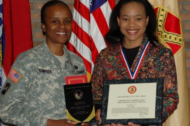 Lt. Col. Fern O. Sumpter, USAG Schinnen Commander, presents the award for Family Member Volunteer of the Year to Lyra Kramer for her work as an Army Family Team Building master trainer instructor and program manager at Schinnen's ACS.