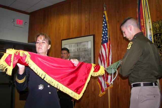 """Brig. Gen. Robin B. Akin, the 3d Sustainment Command (Expeditionary) commanding general, uncases the brigadier general colors with her son, Brian, a member of the Corps of Cadets at Texas A&M University, during her promotion ceremony which was held at the college on Thursday, April 16.  With her promotion, Akin became the first female commander of the 3d ESC and one of only 22 female general officers within the Army. """"The proudest day of my life was my first salute from an NCO as a general officer in front of the Fort Knox PX,"""" said Akin.  """"It was a Soldier that I had Soldiered with in Iraq at MNF-I Headquarters, and he immediately ran up and told me that he knew someday that I would become a general officer. That was one of my proudest moments, having a subordinate say that he knew I would make it."""" (Courtesy Photo)"""