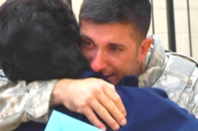 Chief Warrant Officer Michael Wells, HHD, 260th Quartermaster Battalion, hugs his mother upon returning from a year-long deployment in Iraq, April 26.