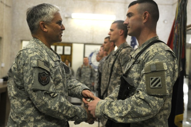 Army Chief of Staff Gen. George W. Casey Jr. gives a coin to Pfc. Mitchell Robertson, 3rd Battalion, 69th Armor Regiment, 1st Advise and Assist Brigade, 3rd Infantry Division, one of five Soldiers to receive a coin from Casey during his visit to COS Falcon, April 28.