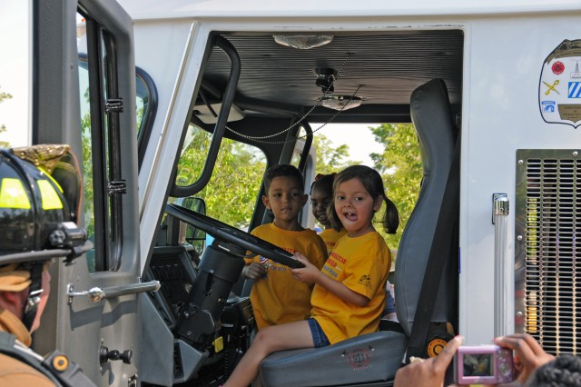 Caitlin Brooks, with the building 403 Child Development Center, takes the steering wheel of a Stewart-Hunter Fire Department fire truck during Wheels Day, April 23. The Month of the Military Child event included static displays of military and emergency vehicles that their mom's and dad's work with every day, giving the kids a chance to see the big vehicles up close.