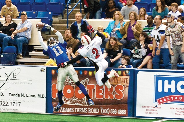 Columbus Lions wide receiver Lonnell DeWalt hauls in a pass Saturday at the Columbus Civic Center as Lafayette Wildcatters defensive back Clarence Pendleton defends.  The Lions won the game 54-26.