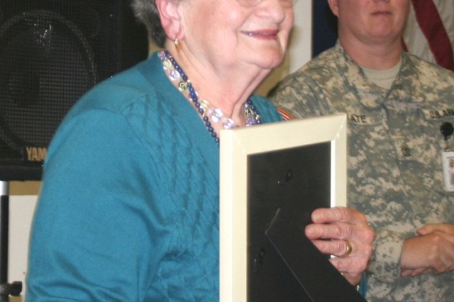 Anna Rado, guest speaker at the Holocaust Days of Remembrance ceremony April 22 at the Hacienda Recreation Center, holds a framed photo of the Fort Sam Houston Quadrangle presented to her as a gift for sharing her story about her imprisonment in the Auschwitz Death Camp in Poland.