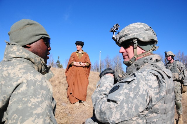 FORT WAINWRWIGHT, Alaska - Sgt. 1st Class Baron Harris from the 5th squadron, 1st Cavalry Regiment, 1st Stryker Brigade Combat Team, 25th Infantry Division speaks with visiting Sgt. Maj. Joseph McFarlane, 5- 1st command sergeant major, as Sgt. Zachary Alsterberg, playing the role of a native village leader, goes about daily routines in order to be seen and reported on by concealed reconnaissance teams.