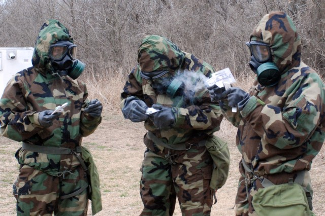 Soldiers of the 168th Brigade Support Battalion use the training version of the M256 chemical agent detector kid to analyze a potential hazard. The kit requires a list of operator actions to complete the process ... and makes hot smoke..