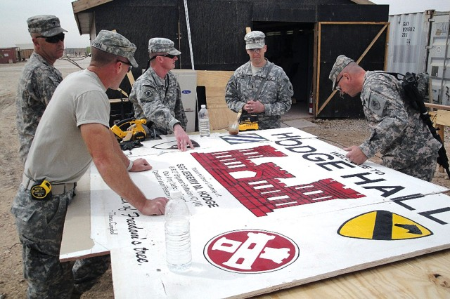 Soldiers from 1434th Engineer Company build a border to protect the Hodge Hall sign on its trip back to the States so that it can be presented to the family of Sgt. Jeremy Hodge, a member of the 612th Engineer Battalion, who was killed in action in October 2005, when an improvised explosive device detonated near his Humvee while on a route-clearance mission.