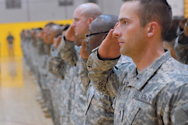 1LT Nathan Wilkes, foreground, and other Soldiers from the 60th Engineer (Vertical) Company salute during a playing of the national anthem.