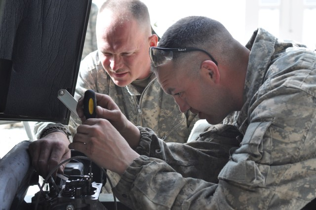 U.S. Army Spc.'s Herbert Mekle and William Crocker, both mechanics for Echo Company, 3rd Battalion, 122nd Infantry Division, Vermont National Guard, repair a three-kilowatt generator used to power communications equipment on Forward Operating Base Thunder, March 22. The Vermont National Guard recently arrived in the Paktya province replacing the Georgia National Guard. (U.S. Army photo)