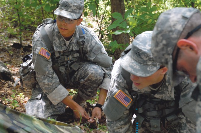 """PVT David Nevarez, left, of 1st Platoon, ties down a stake while helping set up a """"field-expedient"""" hooch."""