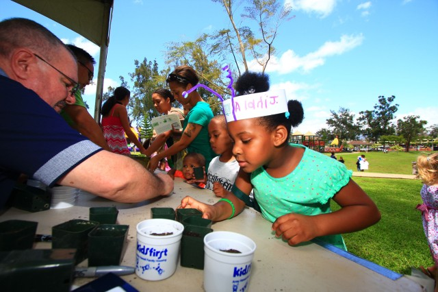 SCHOFIELD BARRACKS, Hawaii - Alani Johnson participates in several make 'n take activities, including planting a seedling that she can take home to nurture and grow. Performance Landscaping donated the seedlings and staff, like Army Hawaii Family Housing's Steve Kirby, left, helped manage the booth.