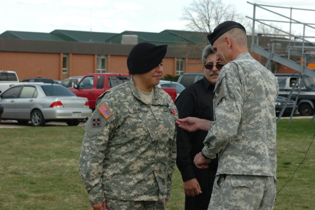 FORT CARSON, Colo. - Brig. Gen. James Pasquarette, deputy commanding general, support, 4th Infantry Division and Fort Carson, pins the Bronze Star Medal with Valor device on Cpl. Helen Ruhl, headquarters and headquarters company, 7O4th Brigade Support Battalion, 4th Brigade Combat Team, 4th Inf. Div. during an awards ceremony at Pershing Field April 21. Ruhl earned the award for her decisive actions under fire while serving in eastern Afghanistan.