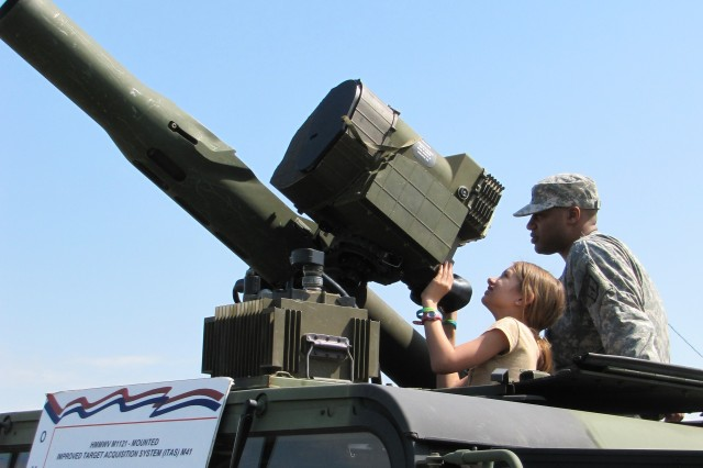 Sixth-grader Rachel Trainer of Columbia Elementary School aims a TOW missile system with the help of an OMEMS Soldier. She is the daughter of Maj. Travis Trainer, the executive officer of the 832nd Ordnance Battalion.