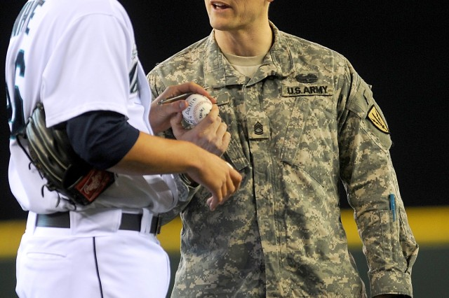Sgt. 1st Class Garth Newell hands Seattle Mariners pitcher Sean White a baseball autographed by his family during the Mariners Salute to the Armed Forces night at Safeco Field in Seattle, April 17.