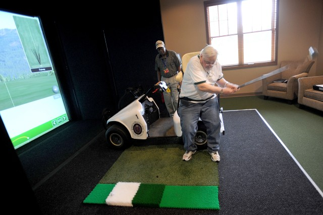 Louis Karamon, a WWII Army veteran, tests his swing in front of a golf simulator in the Rehabilitation and Learning Center at the American Lake Veterans Golf Course April 20.