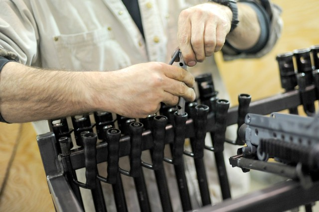 Jack Stevens, a weapons repairer, works on an M-249 at the DOL small arms maintenance facility.
