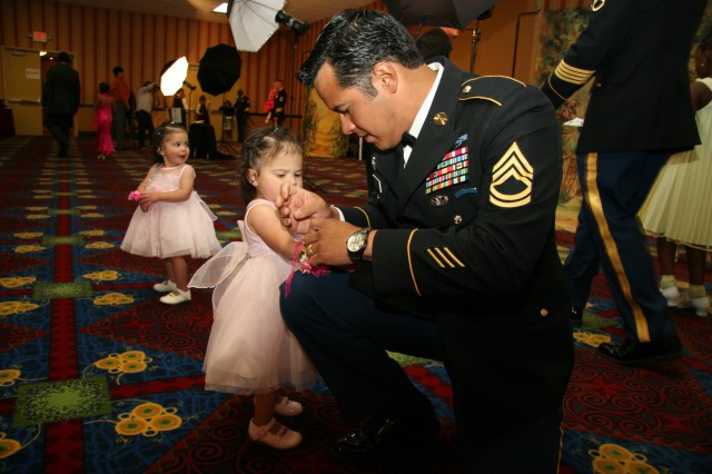 COLORADO SPRINGS, Colo.---Sgt. 1st Class Nelson Grizales, 10th Special Forces Group (Airborne), ties a corsage on the wrist of his 17-month-old daughter, Arianna, prior to having a family photo taken with twin Daniella, left, and sister Isabella, not pictured.