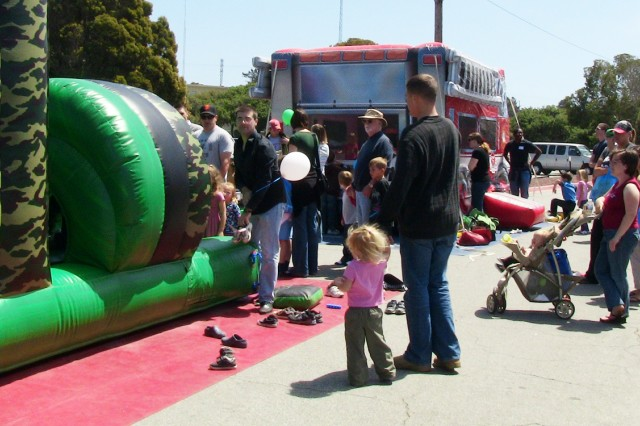 PRESIDIO OF MONTEREY, Calif. - Children and parents stand in line for the bouncy house and other kid-friendly activities during the Celebrating Military Children festival here April 24. The event offered information and activities for community children and their parents.
