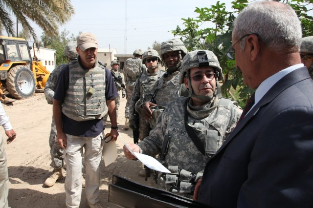 First Lt. Gerardo Aquino, a member of the 1411th Civil Affairs Company from Edison, N.J. currently attached to the 3rd Heavy Brigade Combat Team, 3rd Infantry Division, speaks with a local Iraqi leader following an inspection of a recently completed project at a water treatment facility that has improved efficiency and water quality for over 500,000 residents of Hashimyiah, Iraq.