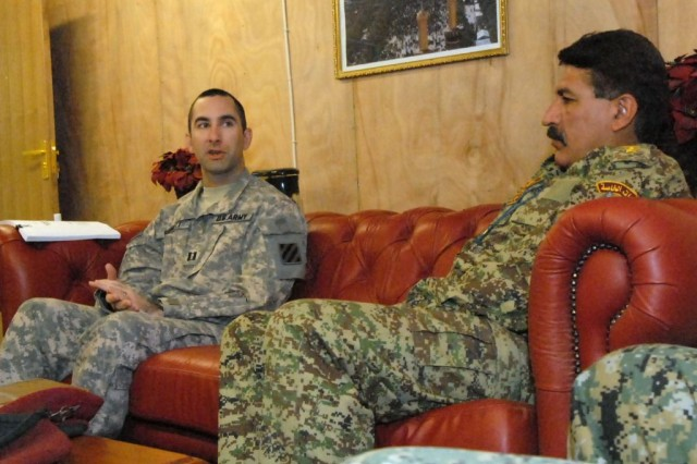 Lt. Col. Salem Mohammed Attar, the public affairs officer for the 8th Iraqi Army Division in Karbala Province, Iraq, (right) listens as Capt. Charles Barrett, the public affairs officer assigned to the 3rd Heavy Brigade Combat Team, 3rd Infantry Division, teaches a class on working constructively with the media at Contingency Operating Site Kalsu, Iraq, April 27. Barrett worked with five of his counterparts in the 8th IA during a five hour public affairs conference.