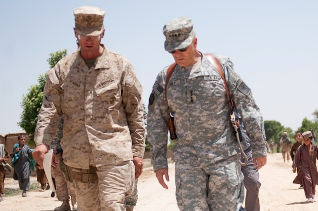 Afghan children walk behind Marine Col. Randy Newman, commander of the 6th Regimental Combat Team, and Chief of Staff of the Army Gen. George W. Casey Jr. as they walk on a main road in Marja, Afghanistan, April 29, 2010.