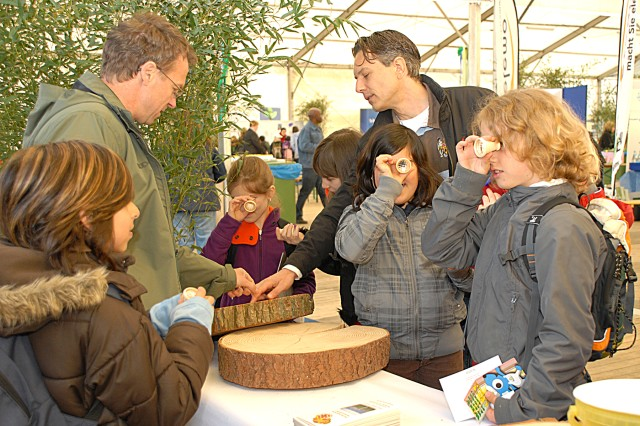 Andreas Ganz, from the German Federal Forestry (left), explains the growth rings of a tree to German students and their teacher. The students are from the Goldwiesen Elementary School in Echterdingen.
