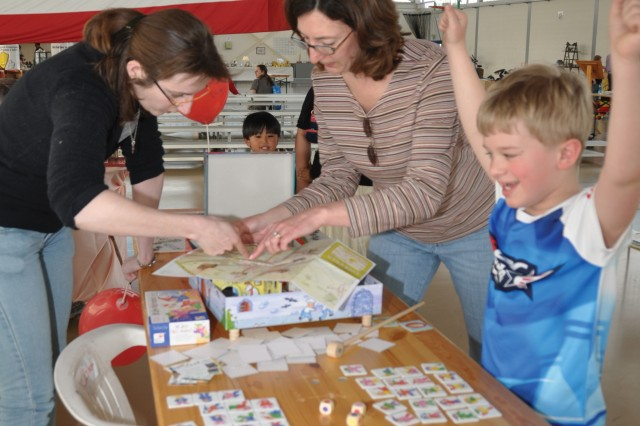 Isabelle Schrauwen gives Kathy Meidlein directions to the game library in ChiAfA..vres as her son, Matthew, celebrates winning a Belgian game. The library rents board games to members for a euro or less.