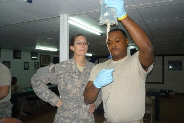 Sgt. Sarah R. Christenson, a Combat Lifesaver instructor with the 445th Transportation Company out of Waterloo, Iowa, 260th Combat Sustainment Supply Battalion, 15th Sustainment Brigade, 13th Sustainment Command (Expeditionary), observes Warrant Officer William Wilkins, the officer in charge of electronics with the 260th CSSB and a Henrico, N.C., native, as he prepares to give an IV during a CLS Course at Camp Liberty, Iraq. (U.S. Army photos by Sgt. Ryan Twist, 139th MPAD, 13th ESC Public Affairs)
