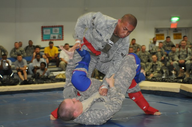 Spc. Billy C. Avery, a supply specialist with the 63rd Ordnance Company out of Fort Lewis, Wash., 80th Ordnance Battalion, 15th Sustainment Brigade, 13th Sustainment Command (Expeditionary) and a Pennington, Texas, native, competes against Air Force Airman 1st Class Keli M. Manglona, a weapons troop with the 57th Aircraft Maintenance squadron out of Nellis Air Force Base, Las Vegas, and a Tinian, Guam, native, April 24 in the Cruiserweight division of the 80th Ordnance Battalion Project Phoenix Combatives Tournament at Joint Base Balad, Iraq.  (U.S. Army photos by Sgt. Ryan Twist, 139th MPAD, 13th ESC Public Affairs)