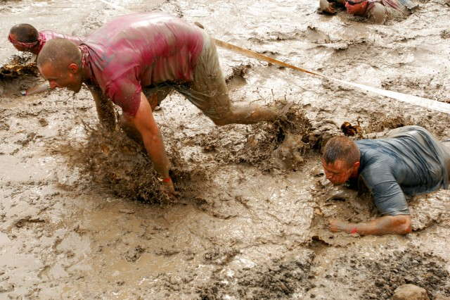 A group of Soldiers low crawl through a stretch of muddy water near the end of an obstacle course at the Family Mud Run near Cowhouse Creek on Fort Hood, Texas May 1. (U.S. Army photo by Pfc. Sean McGuire)