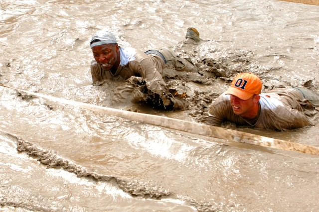 Col. Ron Kirklin, 4th Sustainment Brigade commander, low crawls through a stretch of muddy water near the end of an obstacle course at the Family Mud Run near Cowhouse Creek on Fort Hood, Texas May 1. (U.S. Army photo by Pfc. Sean McGuire)
