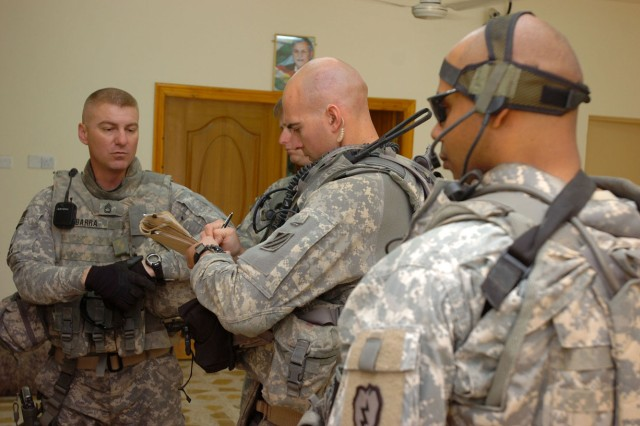 First Lieutenant Stephen Bennie (pictured center with notebook), platoon leader, Task Force Wings' Personnel Recovery Force, 1st Battalion, 64th Armor Regiment, 2nd Brigade Combat Team, 3rd Infantry Division, collects information from a ground force unit working in conjunction with an Iraqi Emergency Response Unit near Kirkuk, Iraq, April 4.