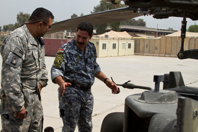 Sgt. 1st Class Christopher Solis, platoon sergeant and maintenance NCO, 2nd Battalion, 159th Aviation Regiment, Task Force Gunslinger, listens as a policeman from the 3rd Iraqi Federal Police Division asks questions regarding the operation and maintenance of the AH-64D Apache attack helicopter at Contingency Operating Site Diamondback in Mosul, Iraq, April 10. The partnership event highlighted the professionalism and leadership of NCOs in the U.S. Army. (Photo by: Capt. Daniel McGurk  2nd Bn., 159th Avn. Regt.)