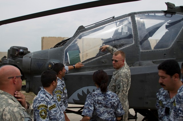 Chief Warrant Officer 4 Beorn Whetstone, an AH-64D Apache attack helicopter pilot, 2nd Battalion, 159th Aviation Regiment, Task Force Gunslinger, explains the capabilities of the AH-64D aircraft to members of the 3rd Iraqi Federal Police Division at Contingency Operating Site Diamondback, in Mosul, Iraq, April 10. The partnership event emphasized the role of the NCO, how to manage a small group of personnel for large missions and learn the basics of the AH-64D Apache attack helicopter. (Photo by: Capt. Daniel McGurk  2nd Bn., 159th Avn. Regt.)